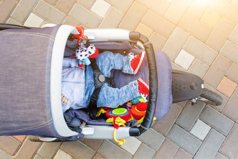 Schlafender dreirädriger Spaziergänger des Babys im Freien Kind im hellen zufälligen Kostüm, das am großen bequemen Pram liegt El stockbilder