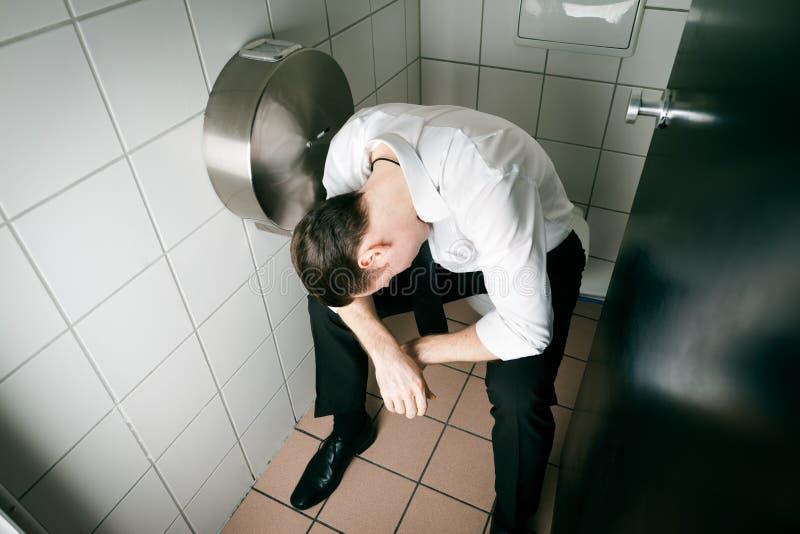 Schlafender getrunkener Mann der Junge auf dem toilette stockbild