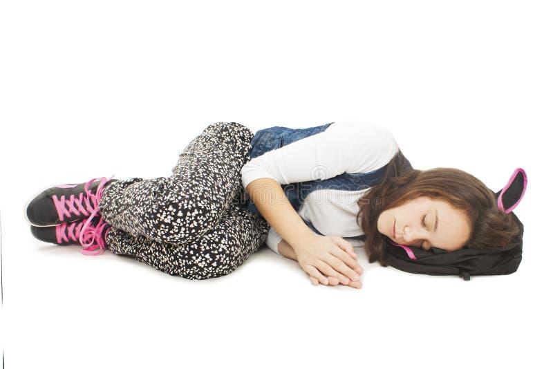 Schlafender Student Schulmädchen, das auf dem Boden, schlafend auf Schultasche liegt stockfotografie