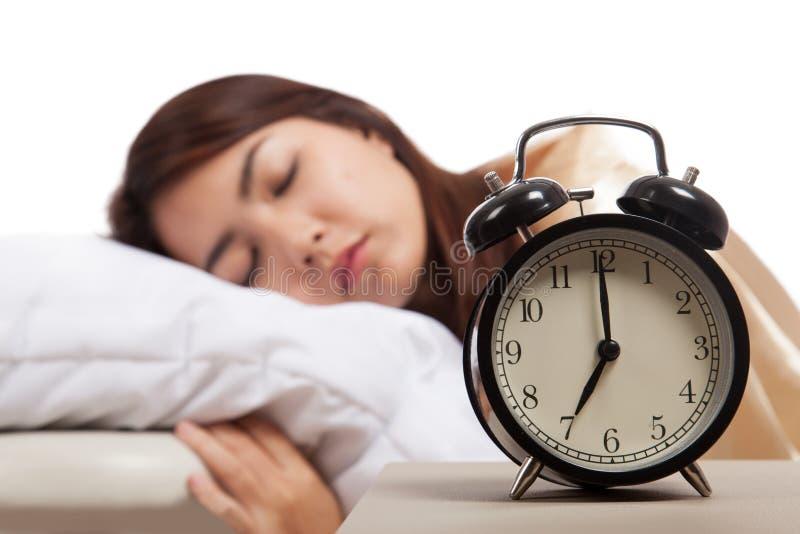 Schlafendes asiatisches Mädchen mit Wecker lizenzfreie stockfotografie