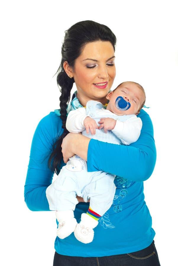 Schlafendes Baby der glücklichen Mutterholding stockfoto