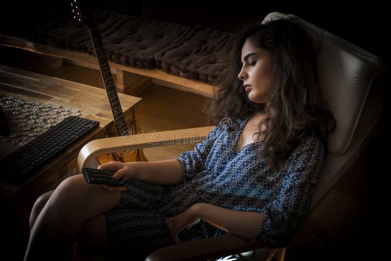 Schlafendes Mädchen auf einem Stuhl mit Fernsehdirektübertragung lizenzfreie stockfotografie