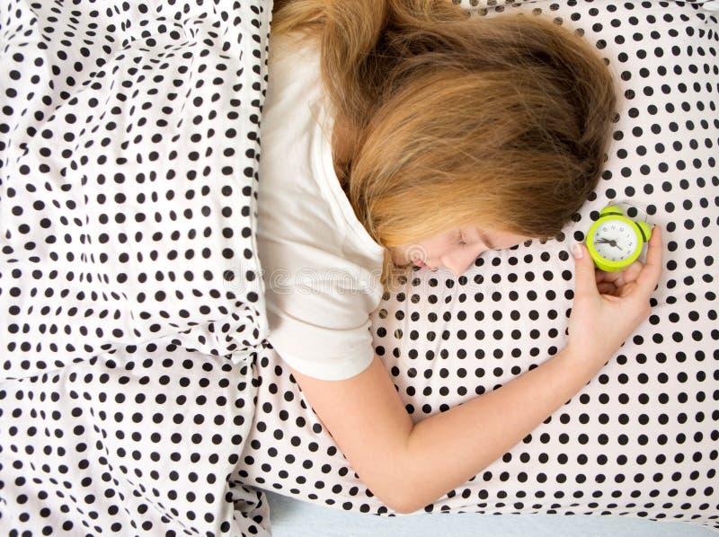 schlafendes Mädchen im Bett mit Wecker, lizenzfreie stockbilder