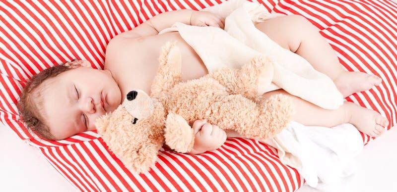 Schlafendes nettes kleines Baby auf den roten und weißen Streifen pillow stockfoto