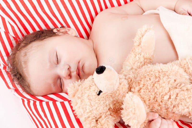 Schlafendes nettes kleines Baby auf den roten und weißen Streifen pillow lizenzfreie stockfotografie