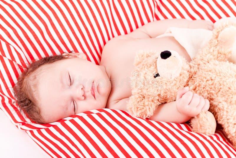 Schlafendes nettes kleines Baby auf den roten und weißen Streifen pillow stockfotografie