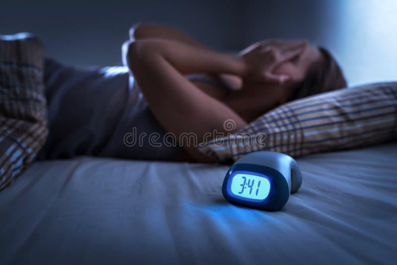 Schlafloses Frauenleiden von der Schlaflosigkeit, von Schlaf Apnea oder vom Druck Müde und erschöpfte Dame Kopfschmerzen oder Mig lizenzfreie stockfotos