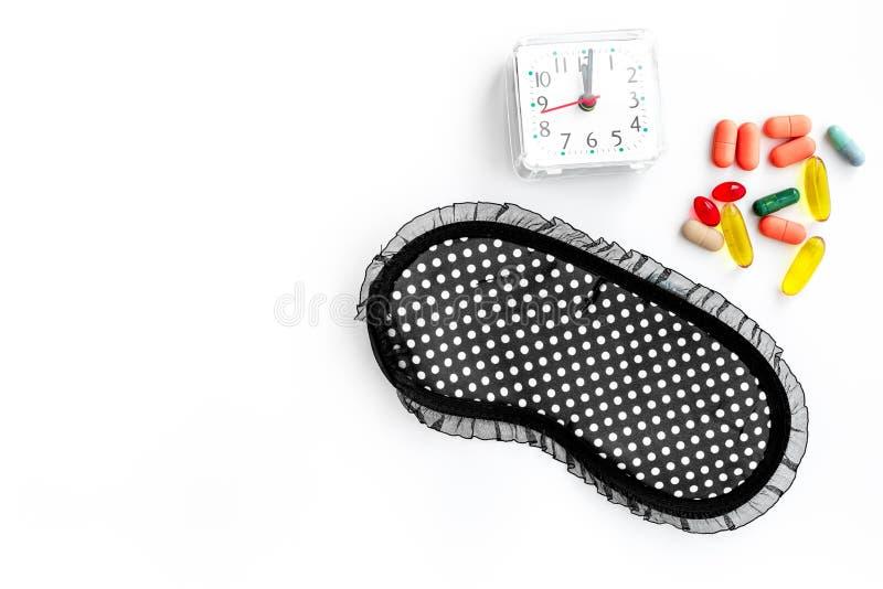 Schlaftabletten für nahe Schlafmaske und -Wecker der Schlaflosigkeit auf weißem copyspace Draufsicht des Hintergrundes stockbild