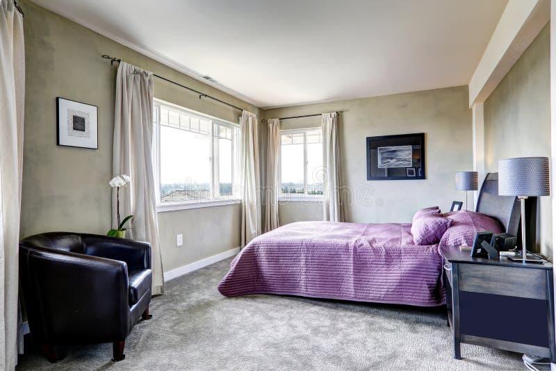 Schlafzimmer in den grauen Tönen mit purpurrotem Bett stockbilder