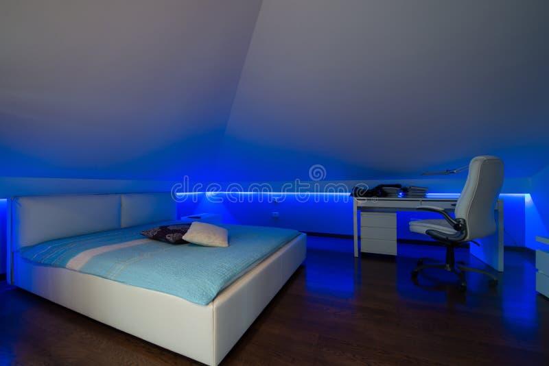Schlafzimmer in der Luxusdachbodenwohnung - geschossen im Restlicht zum highligh lizenzfreie stockbilder