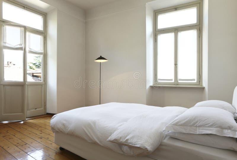 Schlafzimmer mit einem doppelten Bett und Lampen lizenzfreie stockbilder