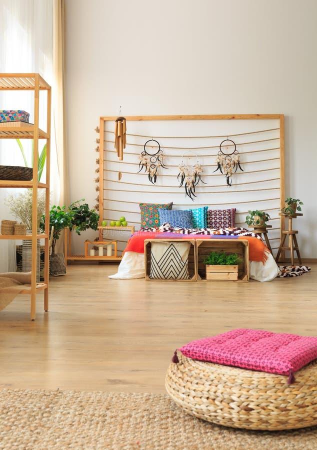 Schlafzimmer mit Regalen und Osmanen lizenzfreies stockbild