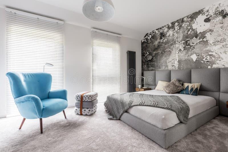 Schlafzimmer mit Weinleseblaulehnsessel stockfoto