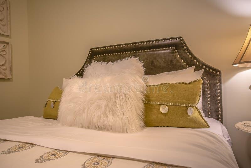 Schlafzimmerinnenraum mit Kissen gegen gepolsterte belgrave Kopfende eines Betts lizenzfreie stockfotografie