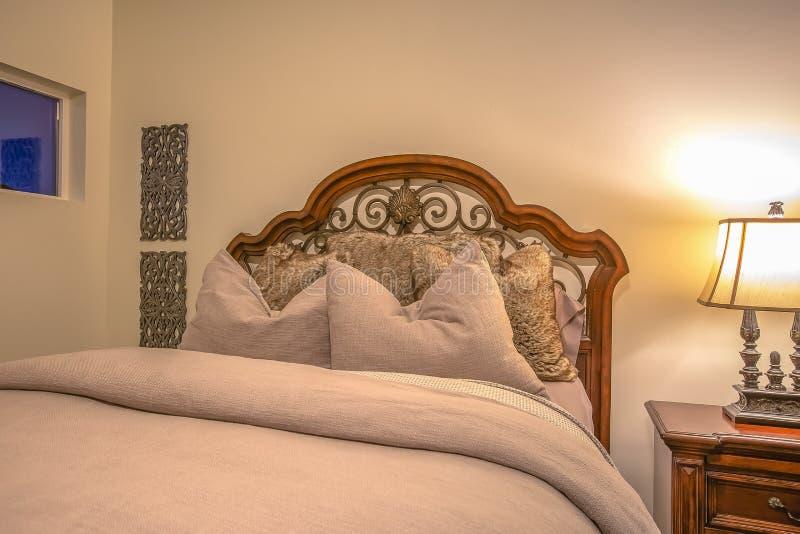 Schlafzimmerinnenraum mit quadratischen Fenstern der Bettlampenseiten-Tabelle und Wanddekorationen stockfotografie