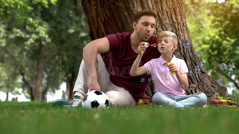 Schlagblasen des sorglosen Jungen, Vater, der mit Sohn im Park, glückliches Wochenende spielt lizenzfreies stockfoto