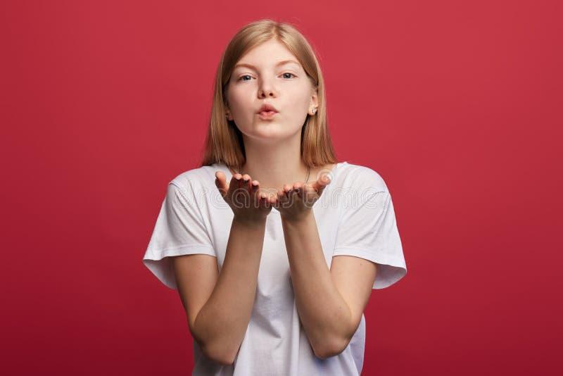 Schlagkuß der jungen attarctive Frau an der Kamera auf dem roten Hintergrund stockbilder