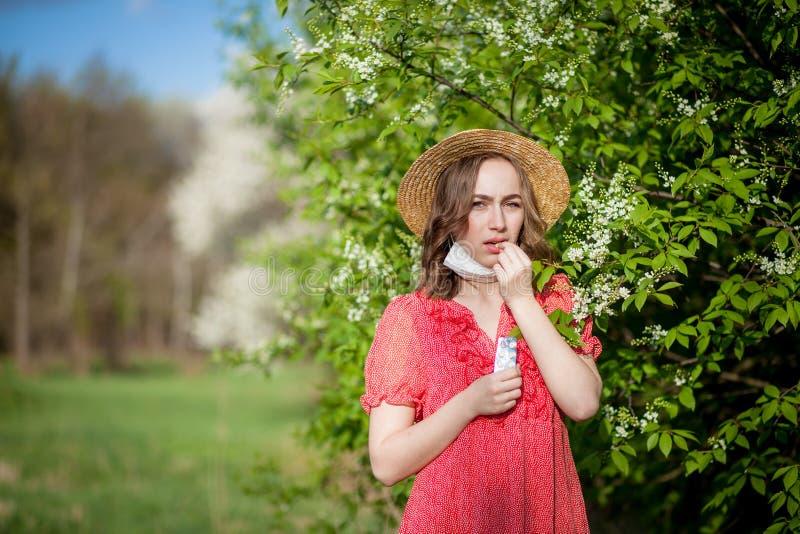 Schlagnase des jungen M?dchens und Niesen im Gewebe vor bl?hendem Baum Saisonallergene, die Leute beeinflussen Sch?ne Dame hat lizenzfreie stockfotografie