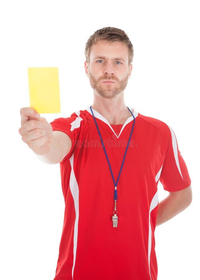 Schlagpfeife des Referenten beim Zeigen der gelben Karte lizenzfreies stockfoto