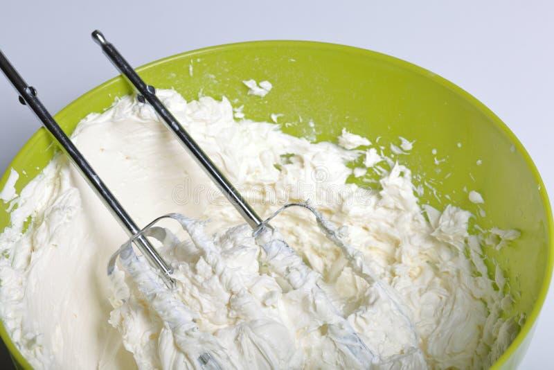 Schlagsahne in einem Behälter In es liegen die Korolla der Mischmaschine Creme für die Verzierung des Kuchens mit Schichten versc lizenzfreie stockbilder