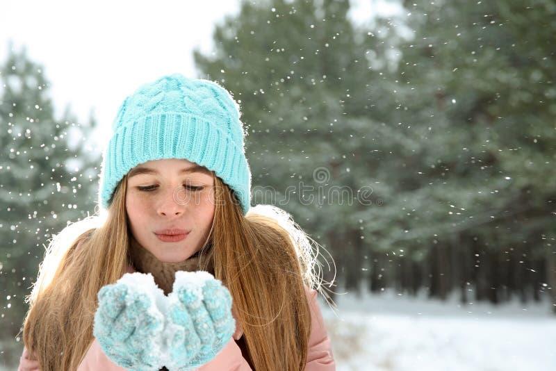 Schlagschnee der Jugendlichen im Winterwald stockbilder