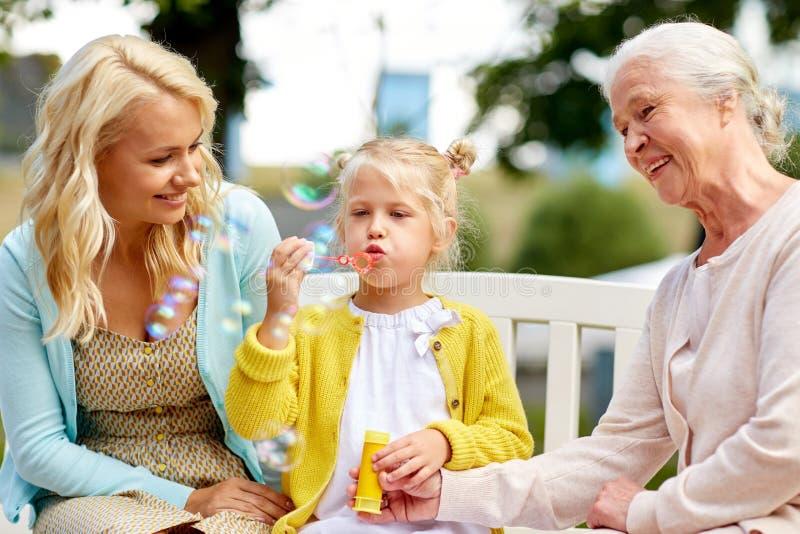 Schlagseifenblasen der glücklichen Familie am Park lizenzfreies stockbild