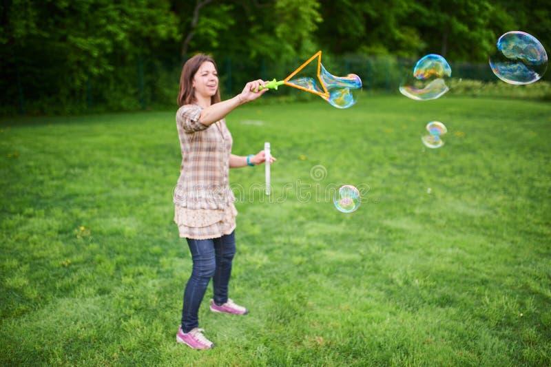 Schlagseifenblasen der jungen Frau auf einem gr?nen Rasen stockbild