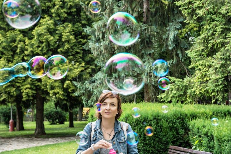 Schlagseifenblasen der jungen kaukasischen Frau im Stadtpark stockfotografie