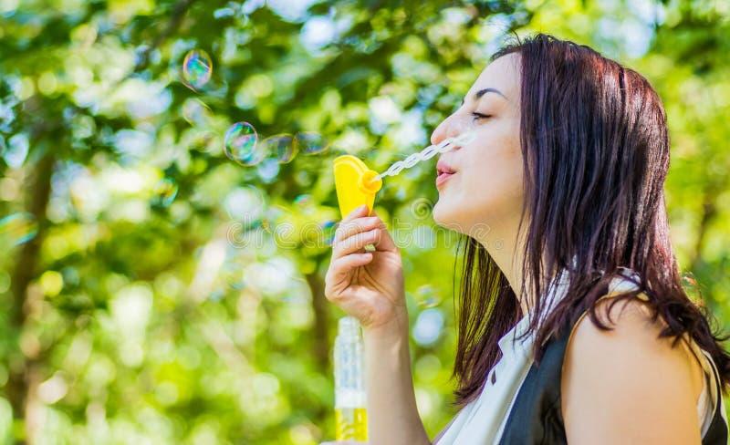 Schlagseifenblasen der kaukasischen Frau im Park lizenzfreies stockfoto