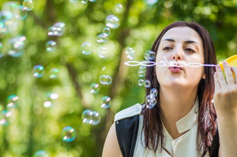 Schlagseifenblasen der kaukasischen Frau im Park lizenzfreies stockbild