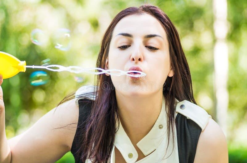 Schlagseifenblasen der kaukasischen Frau im Park stockbild