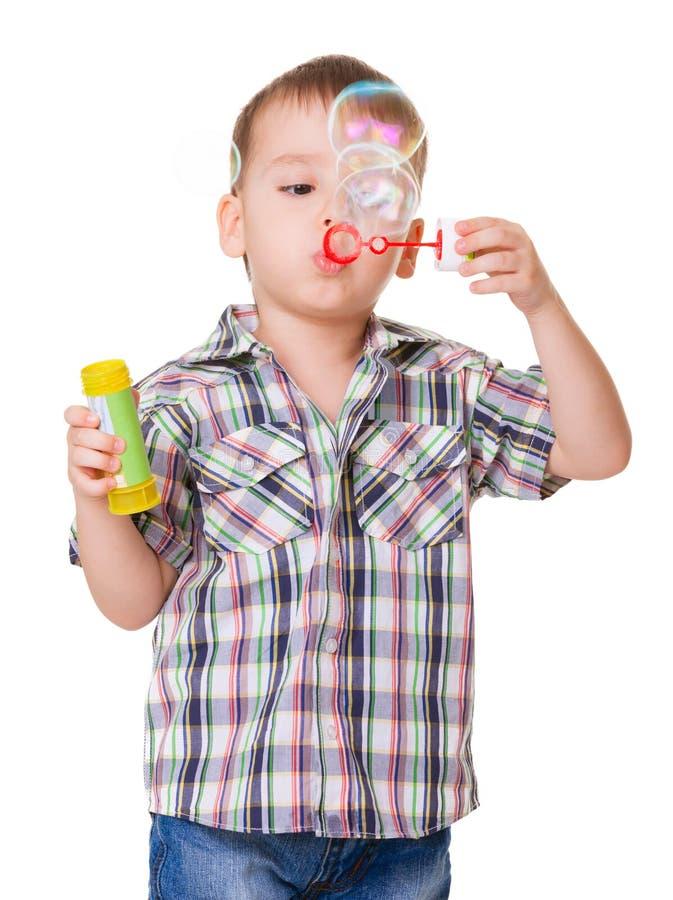 Schlagseifenblasen des Jungen auf Weiß lizenzfreie stockfotografie