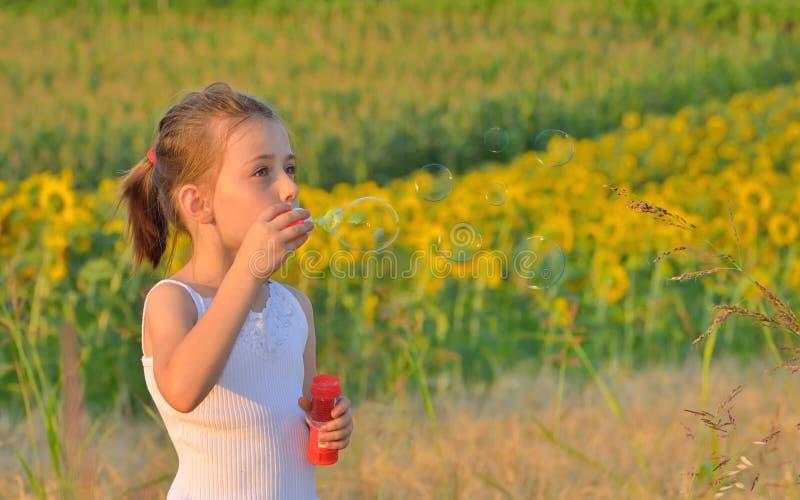 Schlagseifenblasen des kleinen Mädchens stockfotografie