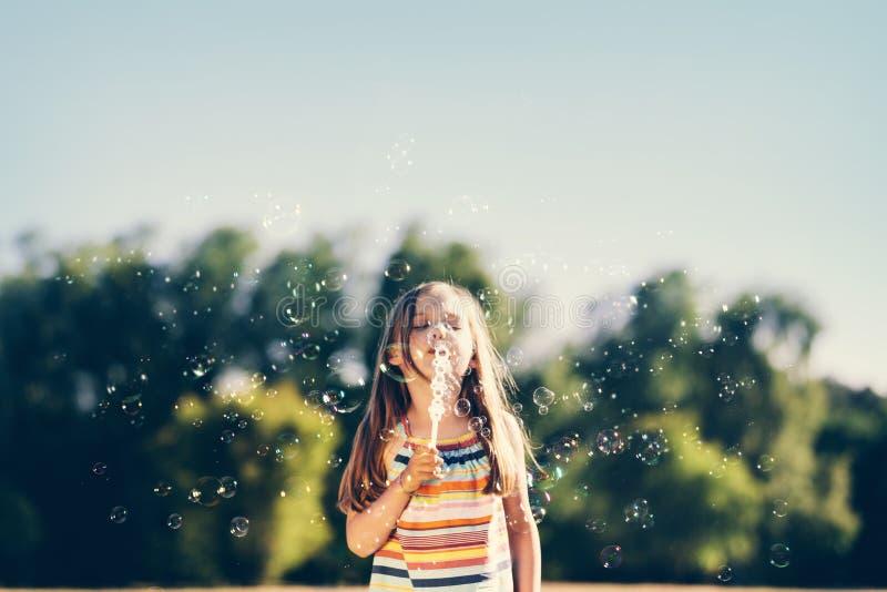 Schlagseifenblasen des kleinen Mädchens im Park lizenzfreie stockbilder