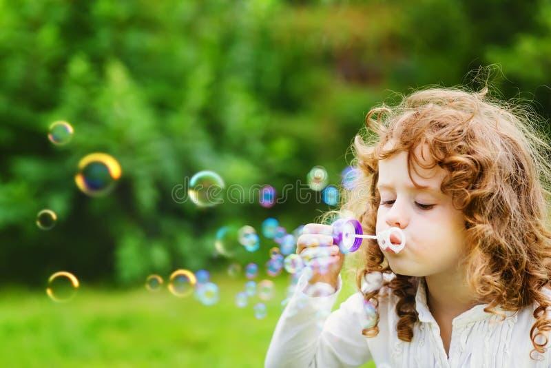 Schlagseifenblasen eines kleinen Mädchens lizenzfreie stockfotos