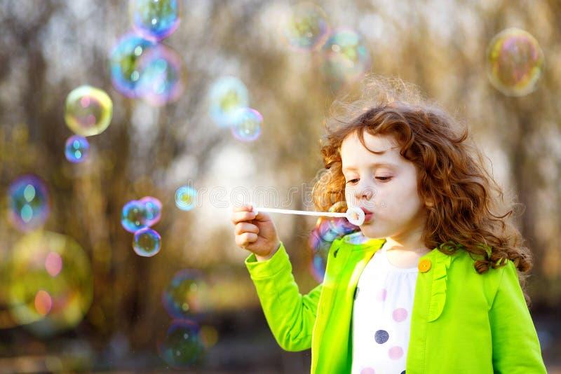 Schlagseifenblasen eines kleinen Mädchens, schönes Cu des Frühlingsporträts lizenzfreie stockbilder