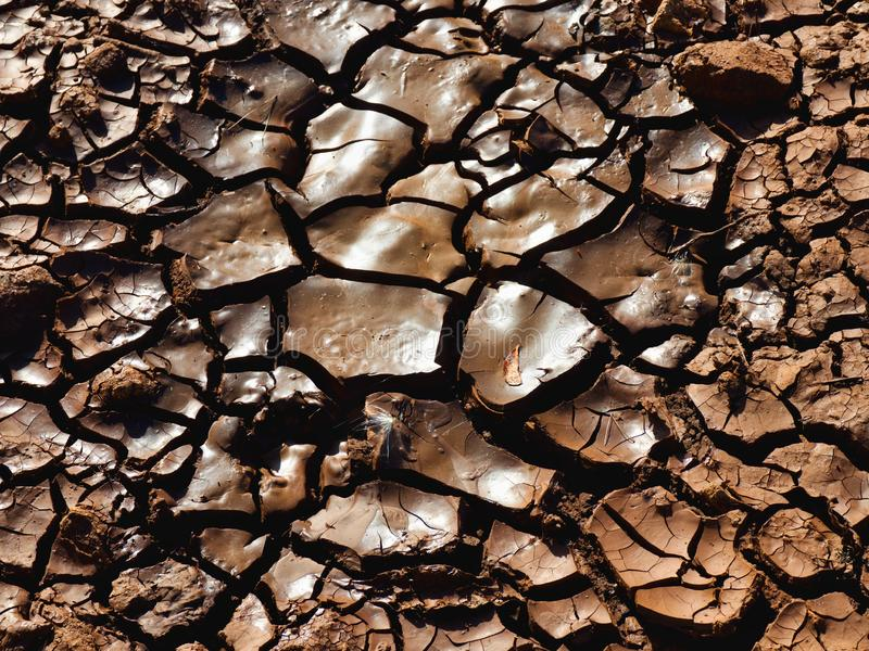 Dry and cracked mud, after a long drought. Dried and cracked mud bottom in mauve brown and deep cracks after a long time without raining on tenerife..Also as a royalty free stock photos