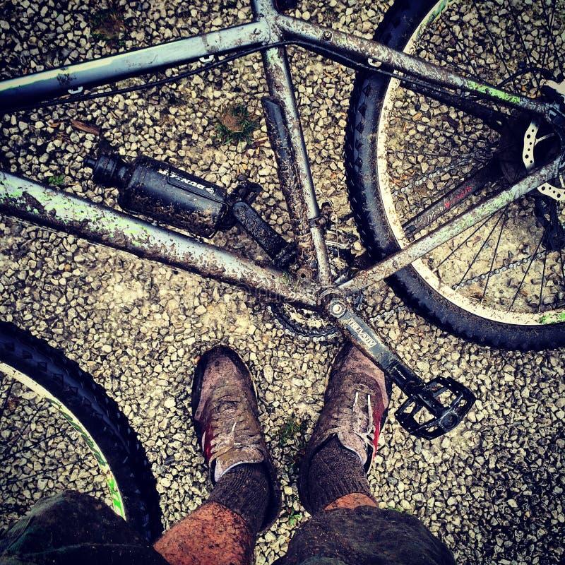Schlammige Mountainbike mit schlammigen Füßen lizenzfreie stockbilder