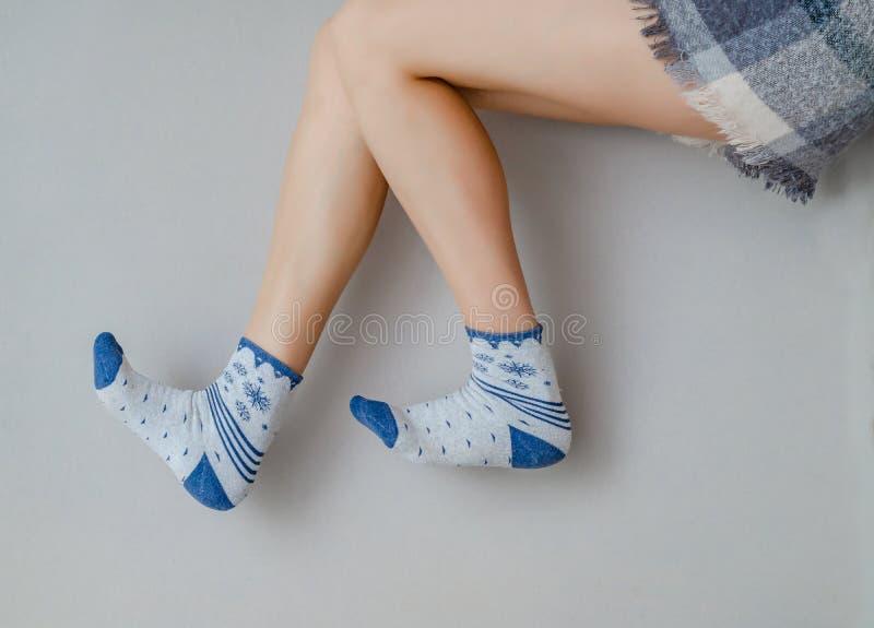 Schlanke Beine einer Frau in Socken, die auf grauem Hintergrund zu den Knien verbogen ist stockfoto