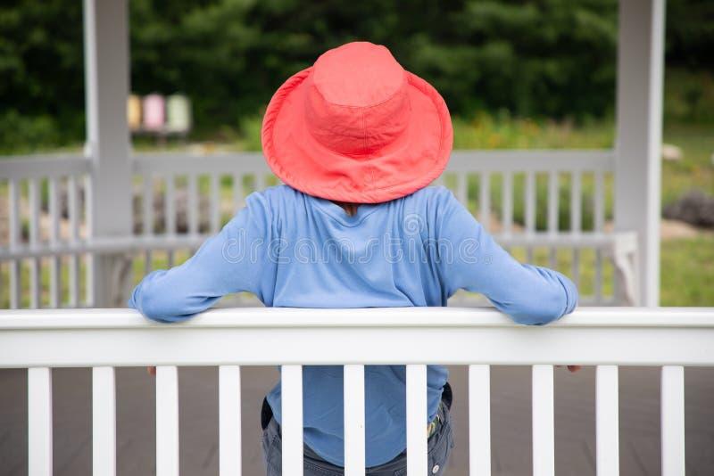 Schlanke Frau im dunklen rosa Hut, der auf weißer Bank im Gazebo betrachtet ihren Garten sitzt stockbilder