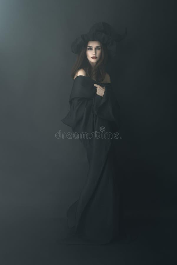 Schlanke Hexe in einem dunklen Nebel stockbilder