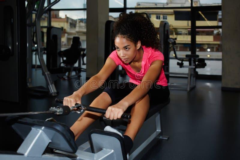 Schlanke junge afroe-amerikanisch Frau, die Übungen tut, um die Rückseite zu verstärken stockfoto
