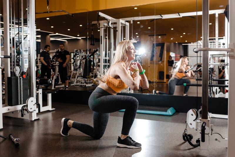Schlankes blondes Mädchen mit dem langen Haar, das in einer Sportkleidung gekleidet wird, tut zurück Hocken in der modernen Turnh lizenzfreie stockfotos