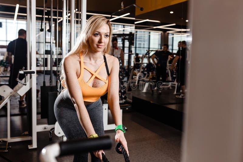 Schlankes blondes M?dchen mit dem langen Haar hat ein TRX-Training in der modernen Turnhalle voll des Sonnenlichtes stockfotos