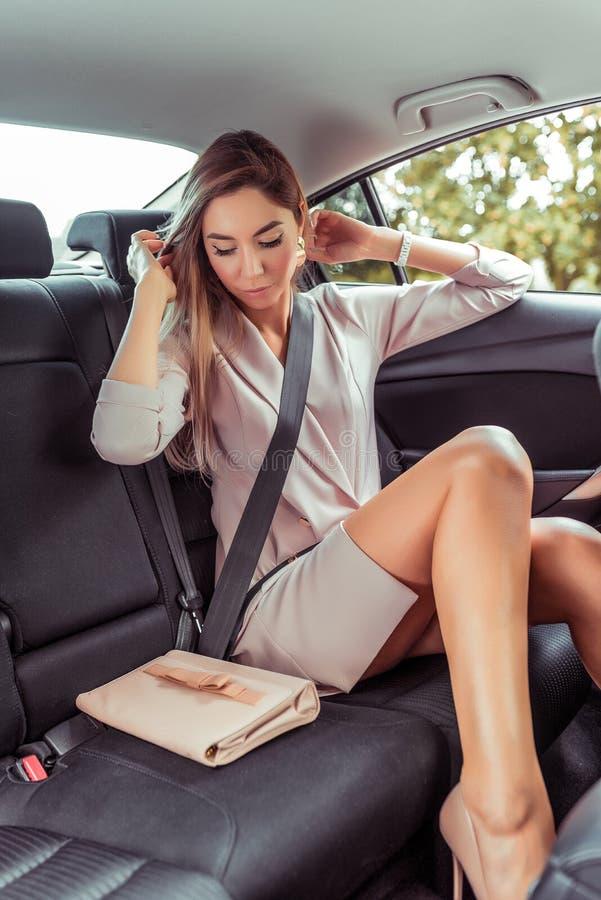 Schlankes gerbtes Mädchen glänzt ihr Haar in VIP-Taxi-Salon, schöne Geschäftsfrau Lady, fährt Taxi Auto-Salon geht stockbild