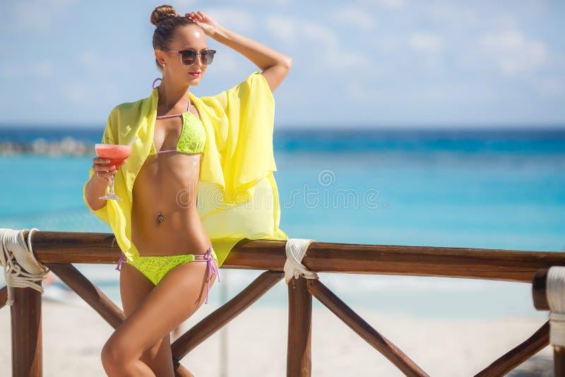 Schlankes Mädchen auf Hintergrund von Ozean mit einem Cocktail lizenzfreie stockbilder