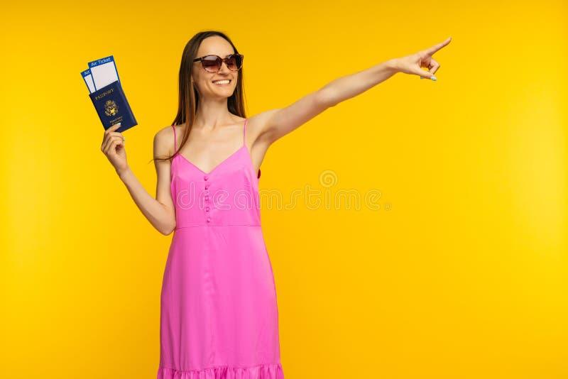 Schlankes Mädchen in einem rosa Kleid und in Sonnenbrille, die Pass mit Flugticket halten und weg zeigen stockfotos