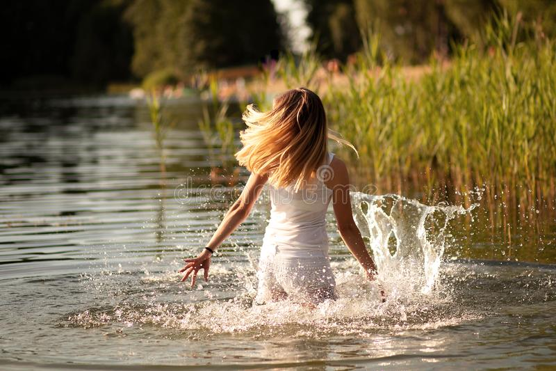 Schlankes Mädchen mit Tanzen des blonden Haares im Wasser am Sonnenuntergang und am Spritzwasser Das Konzept der Freiheit, Glück, stockfoto
