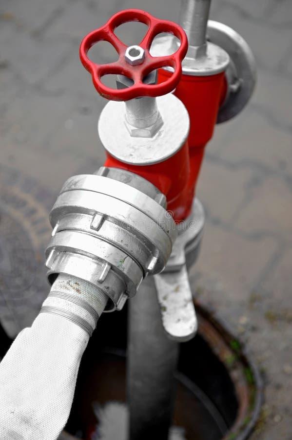 Schlauch angeschlossen an roten Hydranten lizenzfreies stockfoto