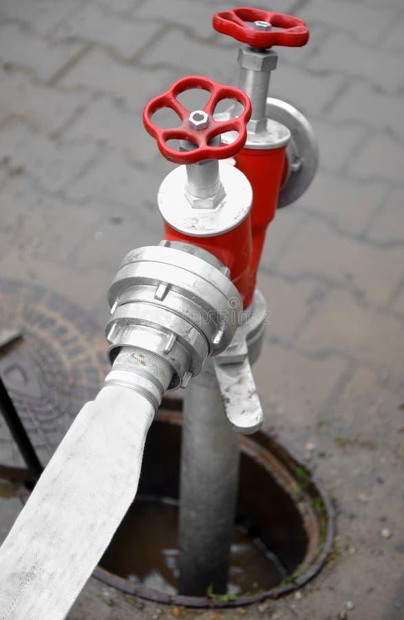 Schlauch angeschlossen an roten Hydranten stockbild